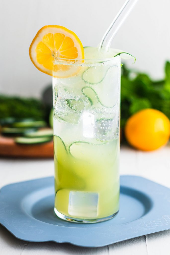 Vertical side shot of iced fizzy drink with a glass straw, cucumber ribbon, and lemon slice sitting on a blue plate and in front of cucumber slices, herbs, and a lemon.