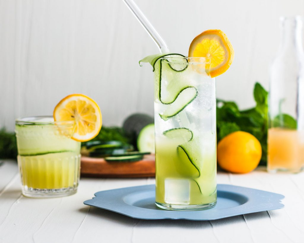 Horizontal side shot of a Lemon Gin Fizz garnished with a cucumber ribbon and lemon slice surrounded by  another drink and in front of cucumber slices, mint leaves, and a lemon.