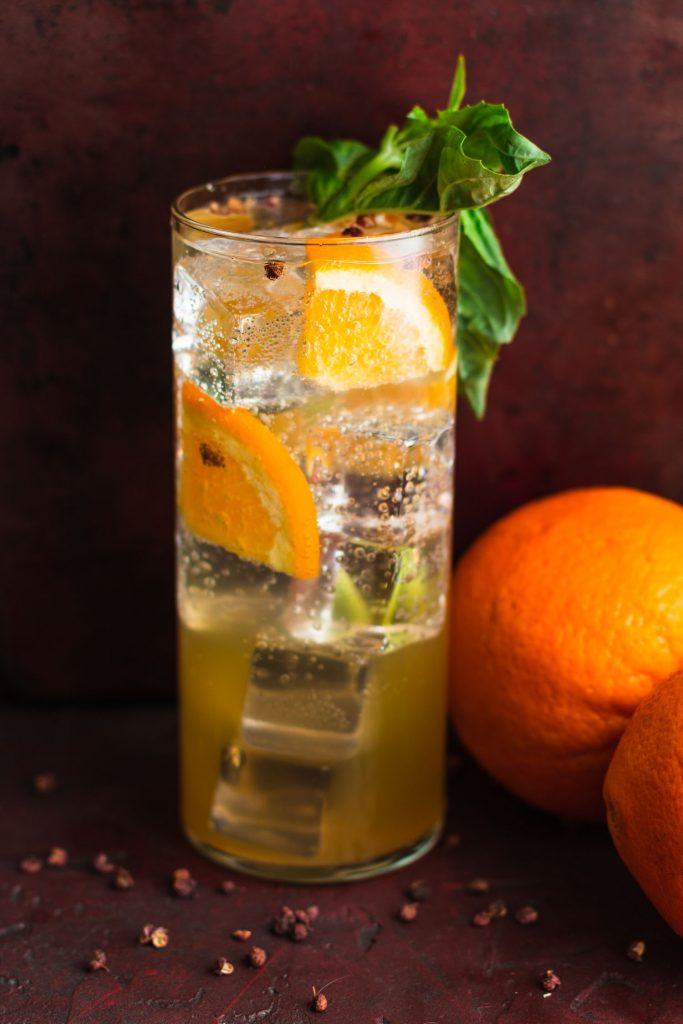 Side shot of a drink with ice, orange quarters, Szechuan peppers, and basil in a highball glass surrounded by oranges.