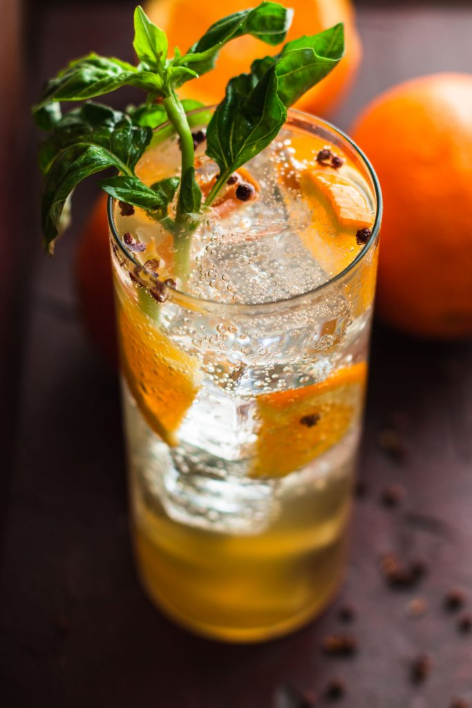 45 degree close up shot of an Orange Gin Fizz in a highball glass with basil and orange garnishes.
