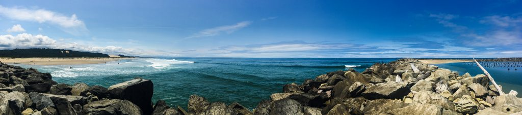 Panorama shot of the beach, ocean, jetty, and oyster farm.