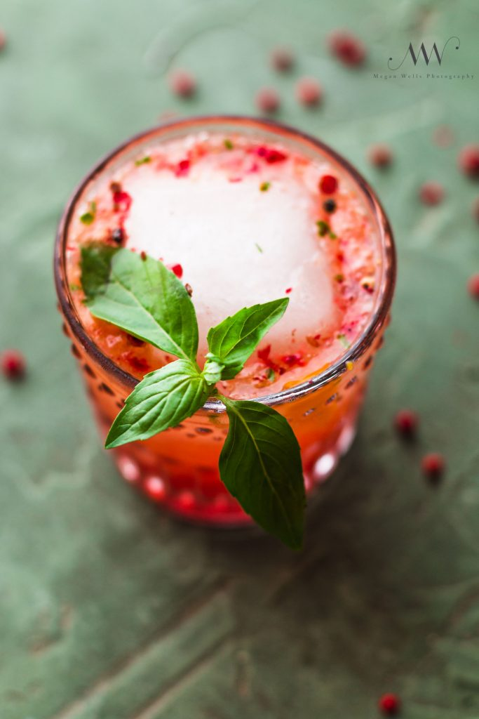 Close up overhead shot of a strawberry mocktail drink in a rocks glass with a large ice cube, basil sprig, and crushed pink peppercorns.