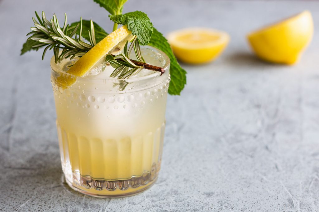 Horizontal side shot of a drink in a rocks glass garnished with a lemon slice and sprigs of rosemary and mint in front of a halved lemon.