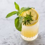 Vertical 45 degree shot of a Rosemary & Mint Lemonade Mocktail in a rocks glass garnished with a sprig of rosemary and mint and a lemon slice.