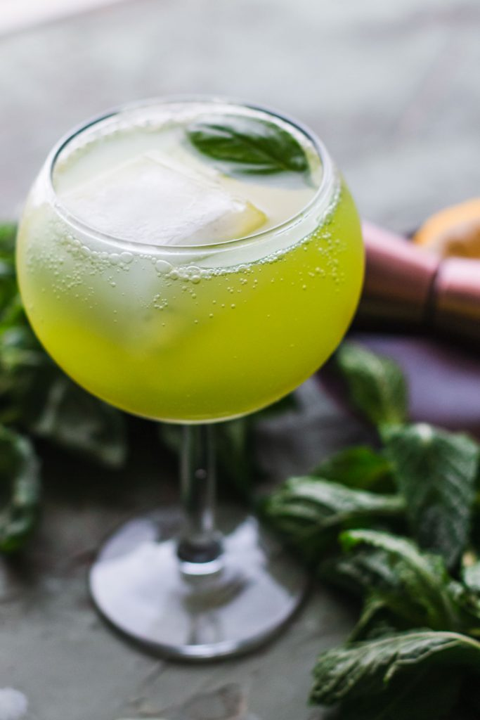 Close up vertical side shot of a Sparkling Basil Lemon Mocktail in a glass goblet with a large ice cube, basil leaf, and surrounded by basil leaves, and a copper jigger.