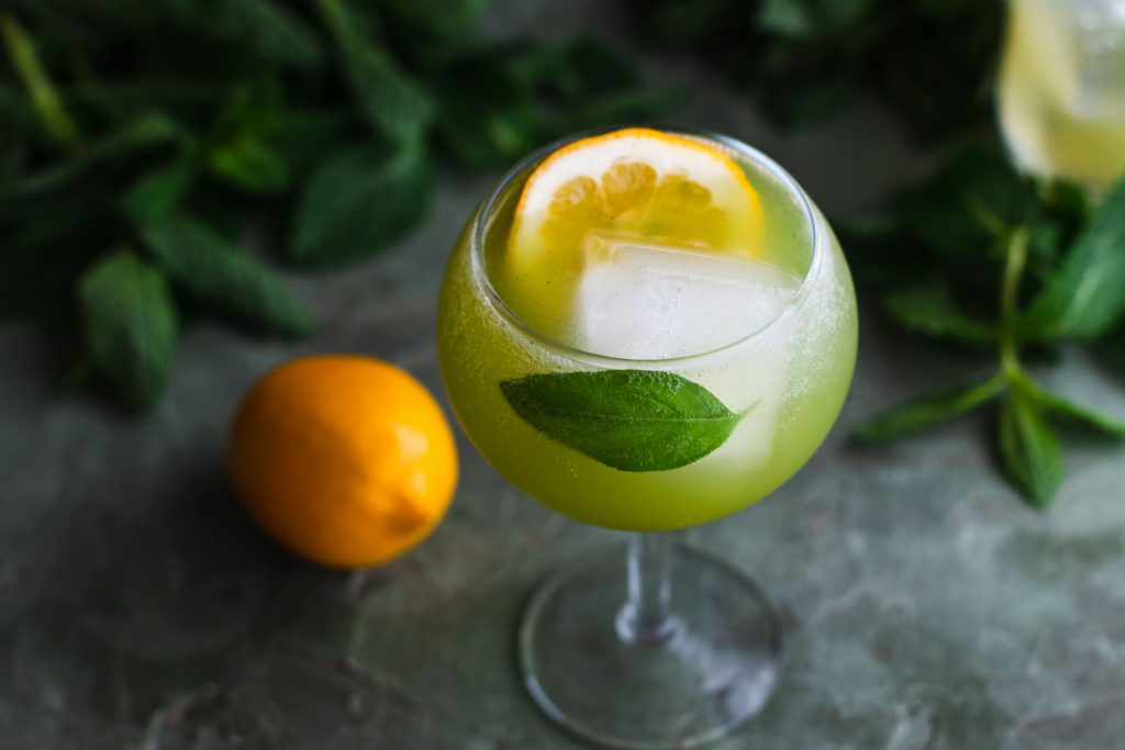 Horizontal 40 degree shot of a basil mocktail in a glass goblet with a large ice cube, lemon slice, basil leaf surrounded by basil leaves and a lemon.