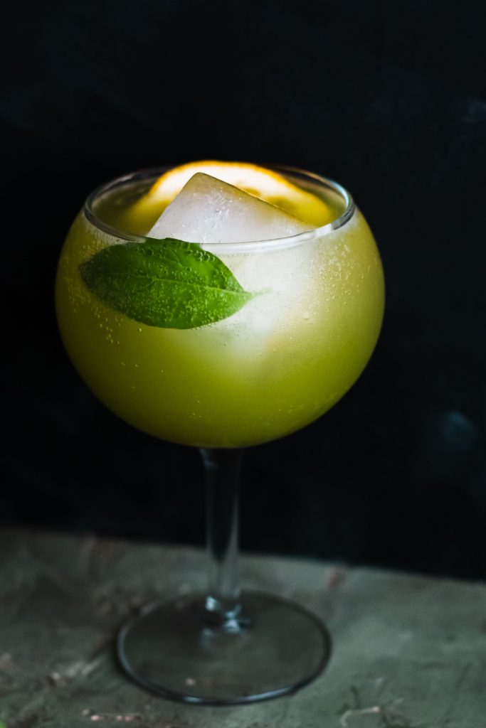 Vertical side shot of a Sparkling Basil Lemon Mocktail in a glass goblet with a large ice cup, lemon slice, and basil leaf.