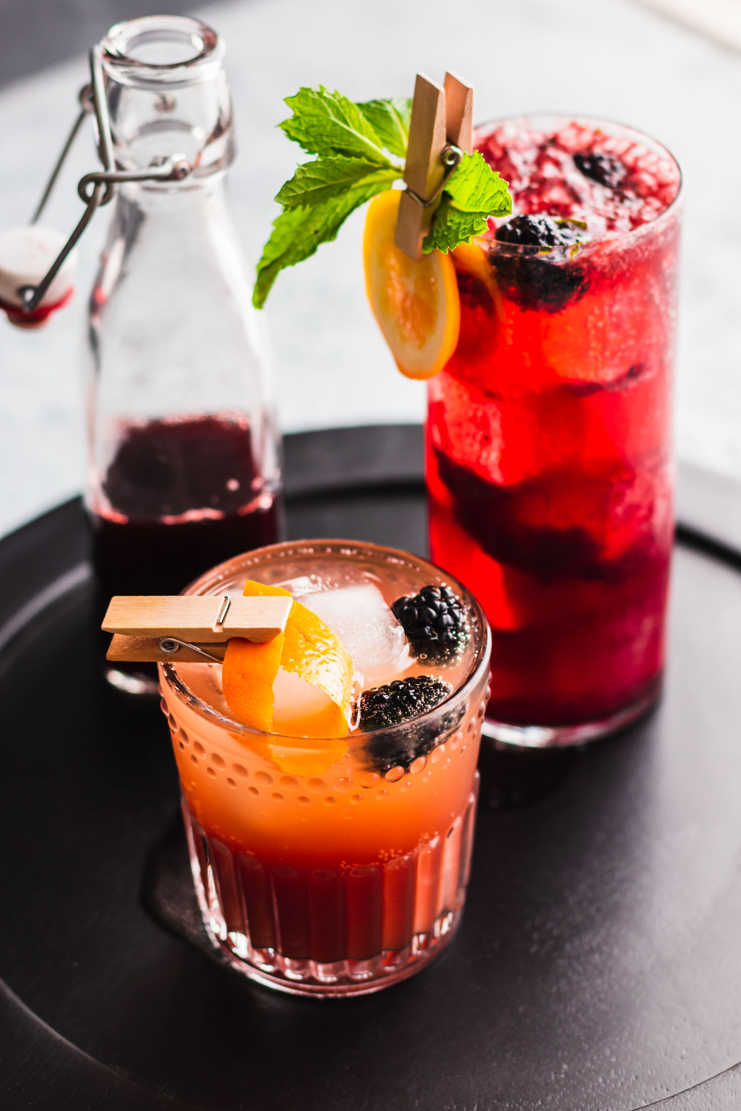 Vertical side shot of a Vanilla Earl Grey Blackberry Mocktail in a rocks glass in front of a drink in a highball glass and a bottled shrub.