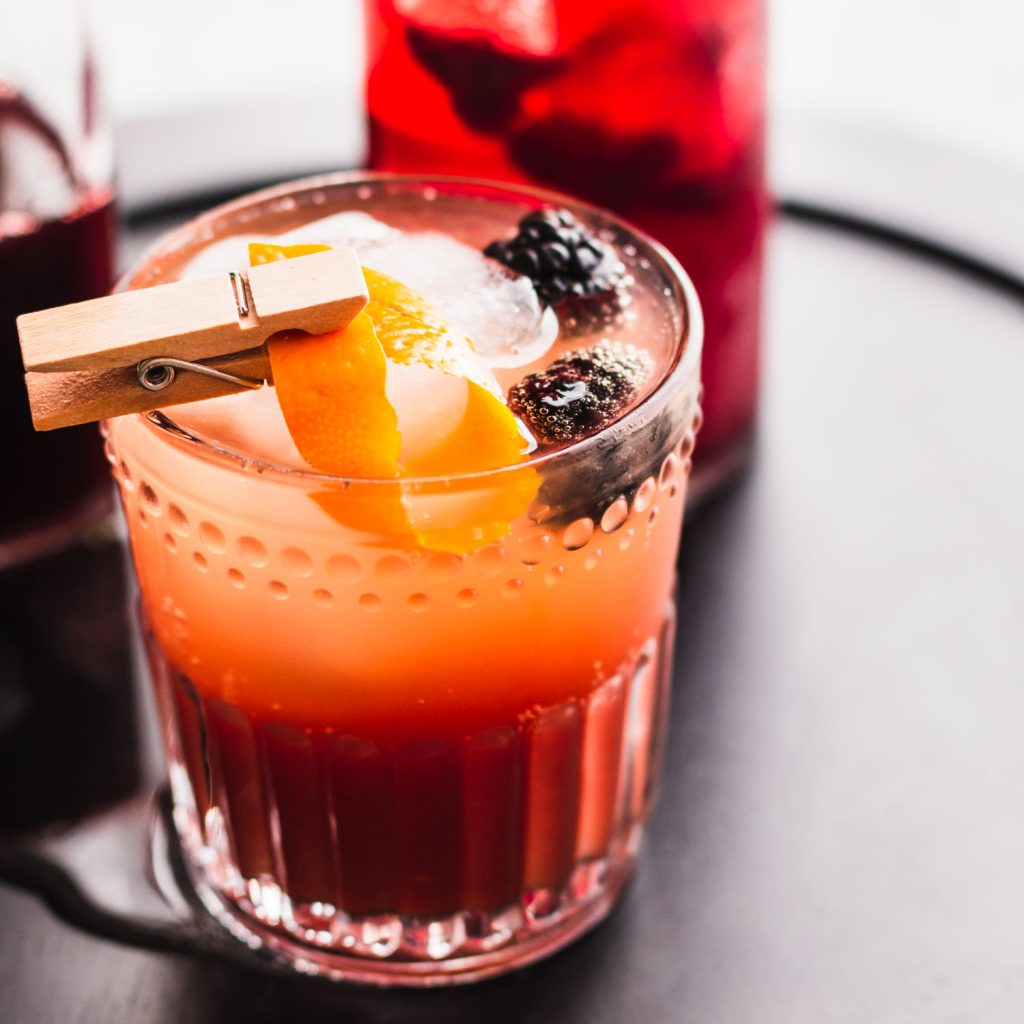 Close up side angle shot of a mocktail in a rocks with a large ice cube, two blackberries, and a clothespin clipping an orange peel over the drink.