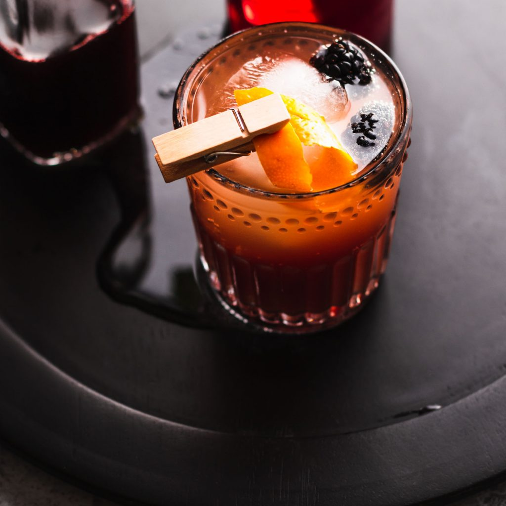 Slight overhead shot of a mocktail in a rocks glass with a large ice cube, two blackberries, and a clothespin clipping an orange peel over the drink.