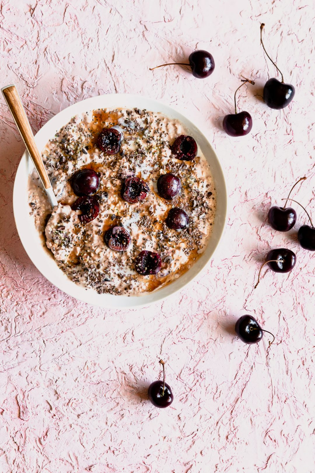Overhead shot of Cherry Overnight Oats in a bowl with a spoon surrounded by cherries.