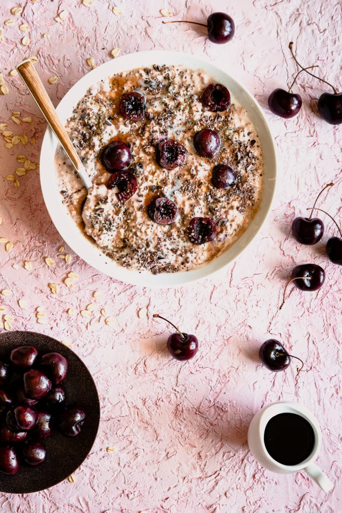 Over head shot of cherry overnight oats in a bowl with a spoon topped with cherries and surrounded by oats, cherries, and a maple syrup in a pourer.