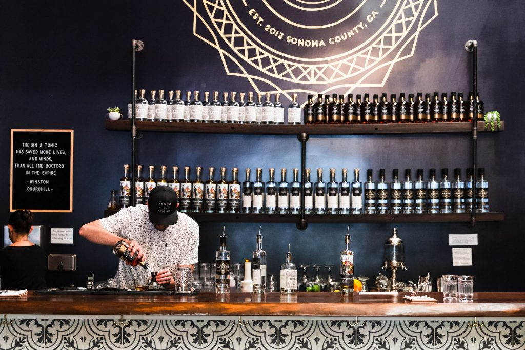 Horizontal show of Young and Yonder Spirits tasting bar with a man pouring alcohol into a shot glass.