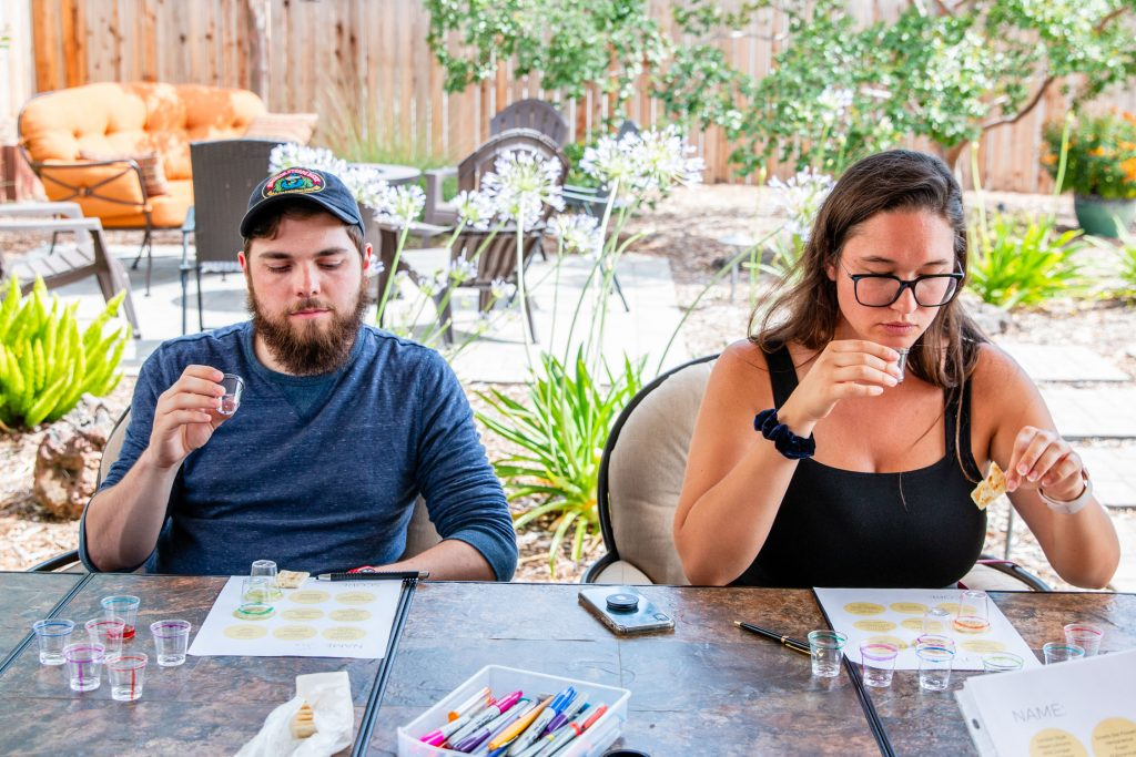 Horizontal shot of a man and woman tasting gin out of plastic shot glasses with a tasting sheet in front of them.