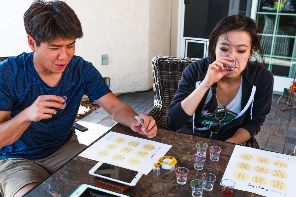 A man and woman tasting gin out of plastic shot glasses.