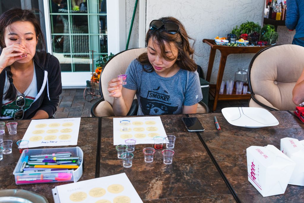 Horizontal shot of two woman doing a blind gin tasting.