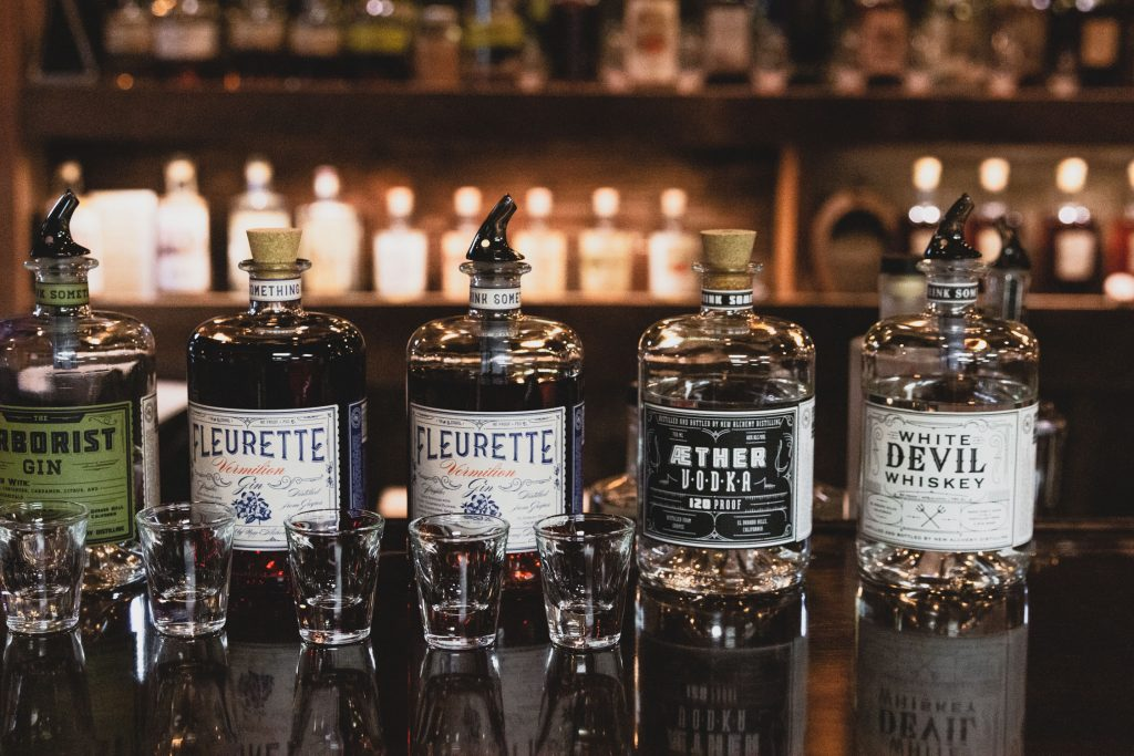 Horizontal shot of New Alchemy Distilling's spirits lined up at a bar with shot glasses in front.