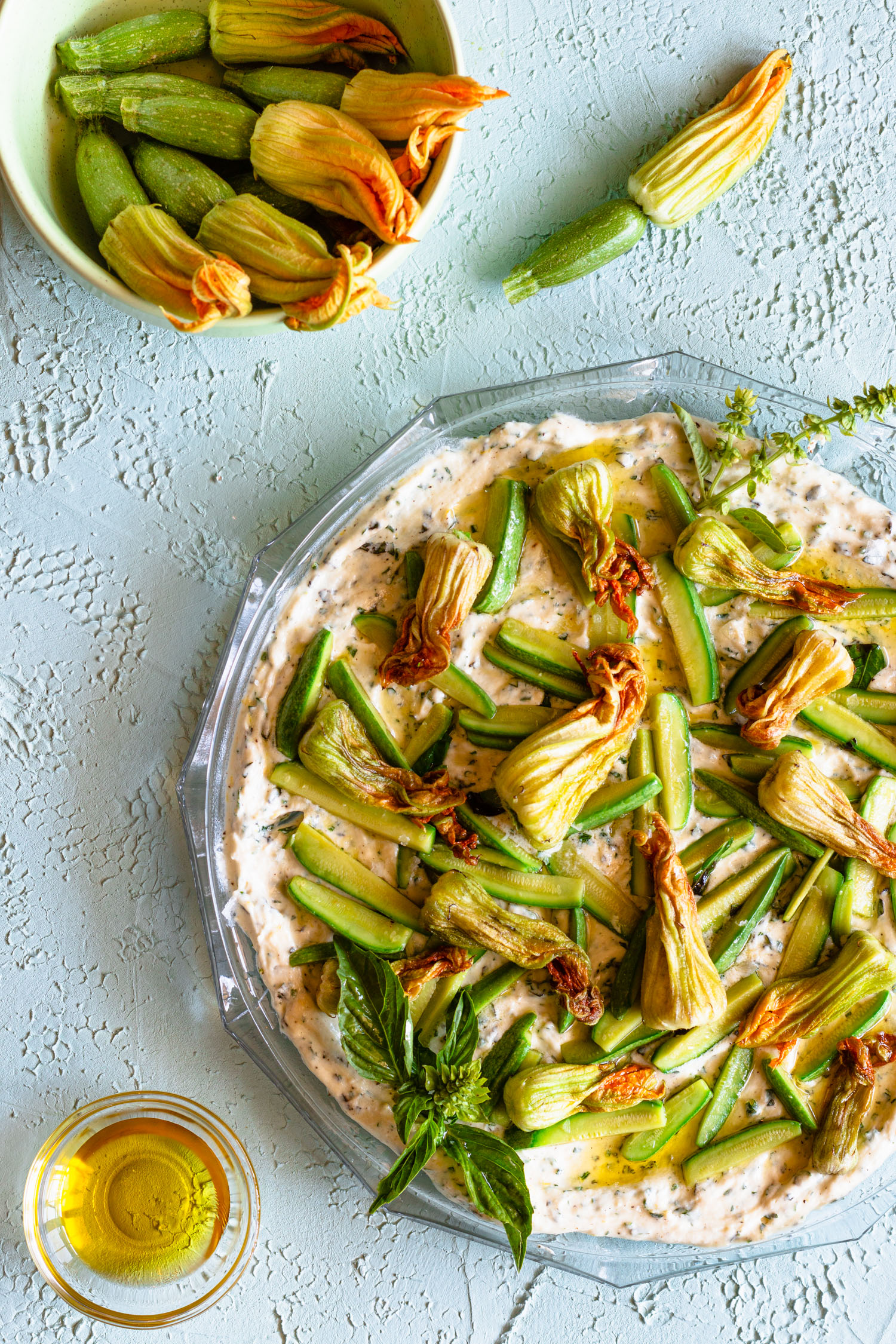 Overhead shot of sautéed zucchini blossoms and herbed ricotta on a serving platter next to a bowl filled with zucchini blossoms and a smaller bowl filled with olive oil.