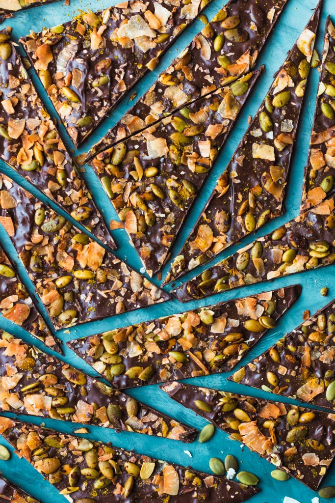 Overhead shot of broken up pieces of easy chocolate bark topped with curry powder, toasted coconut, and oven roasted pepitas.