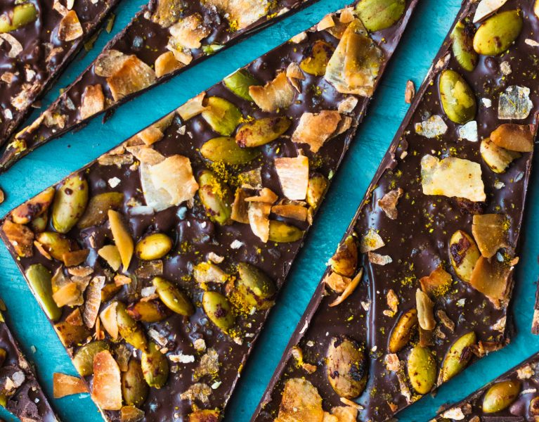 Close up overhead shot of broken up pieces of easy chocolate bark topped with curry powder, pepitas, and coconut flakes.