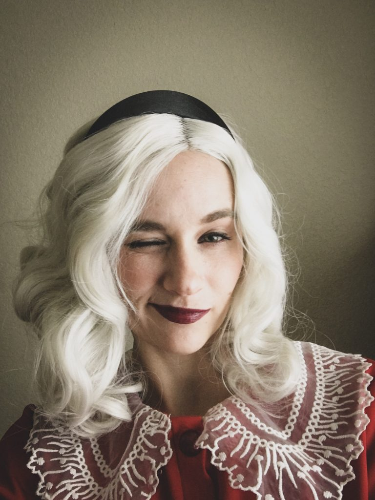 Image of a woman in a Sabrina Spellman halloween outfit, winking.