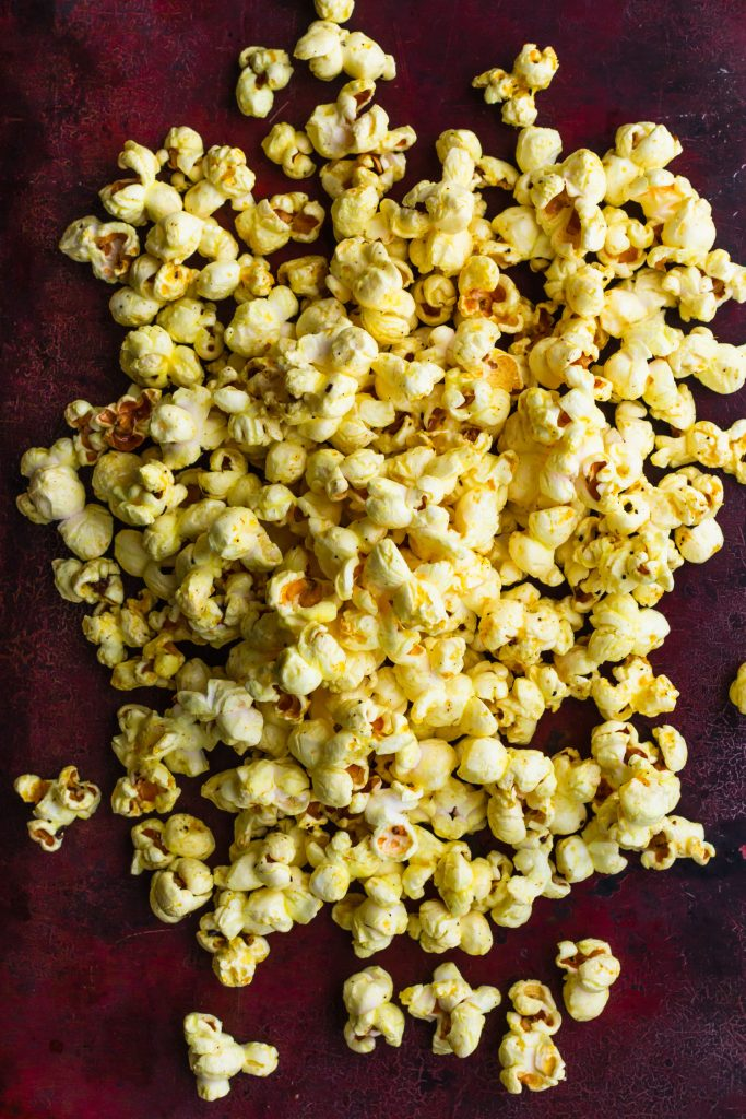 Overhead shot of a pile of Thai yellow curry popcorn on a baking sheet.