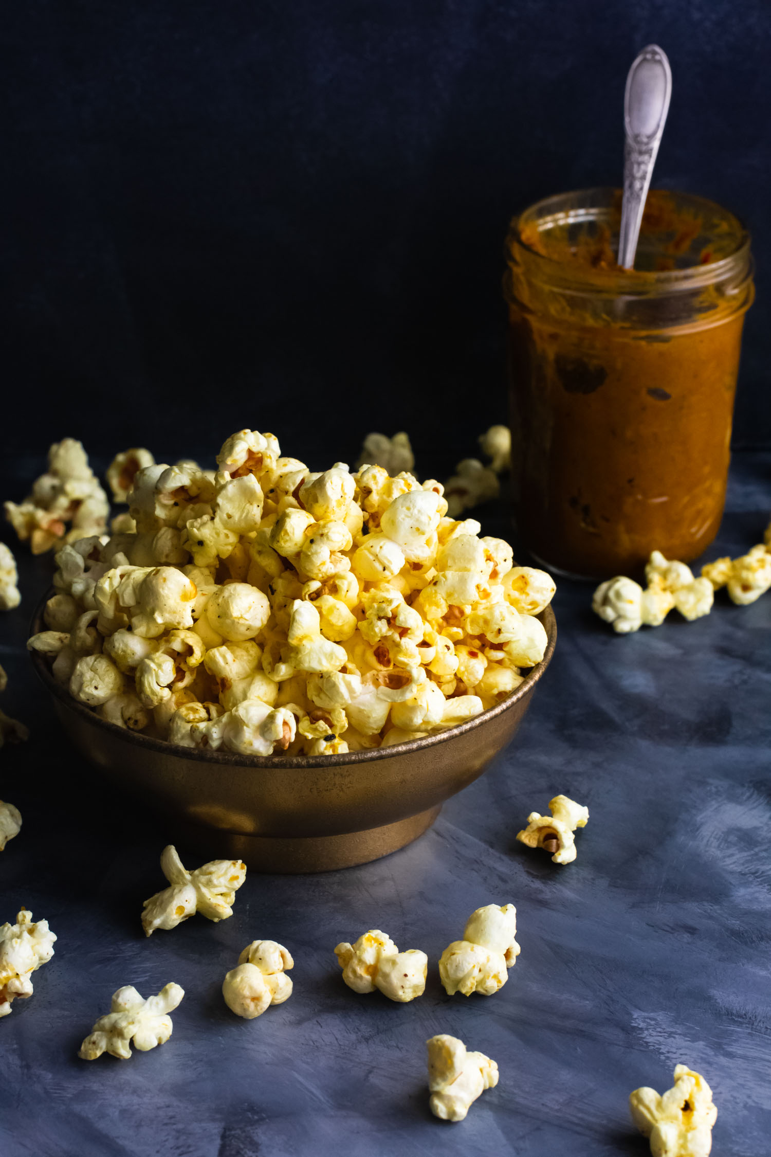 Vertical Shot of popcorn overflowing from a bowl with a mason jar of curry in the background.