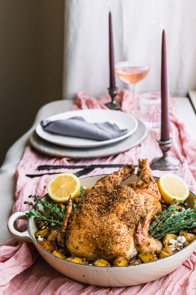 Side vertical shot of roasted feta brined chicken with potatoes and chickpeas in a skillet on a table setting with candles, plates, and glasses.