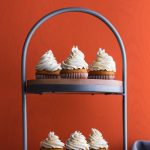 6 frosted sweet potato cupcakes on a two level wood and metal rustic cupcake stand with a napkin to the side.