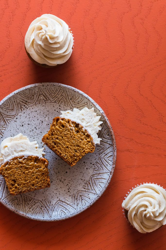 Overhead shot of a halved sweet potato cupcake on a plate surrounded by two other cupcakes.
