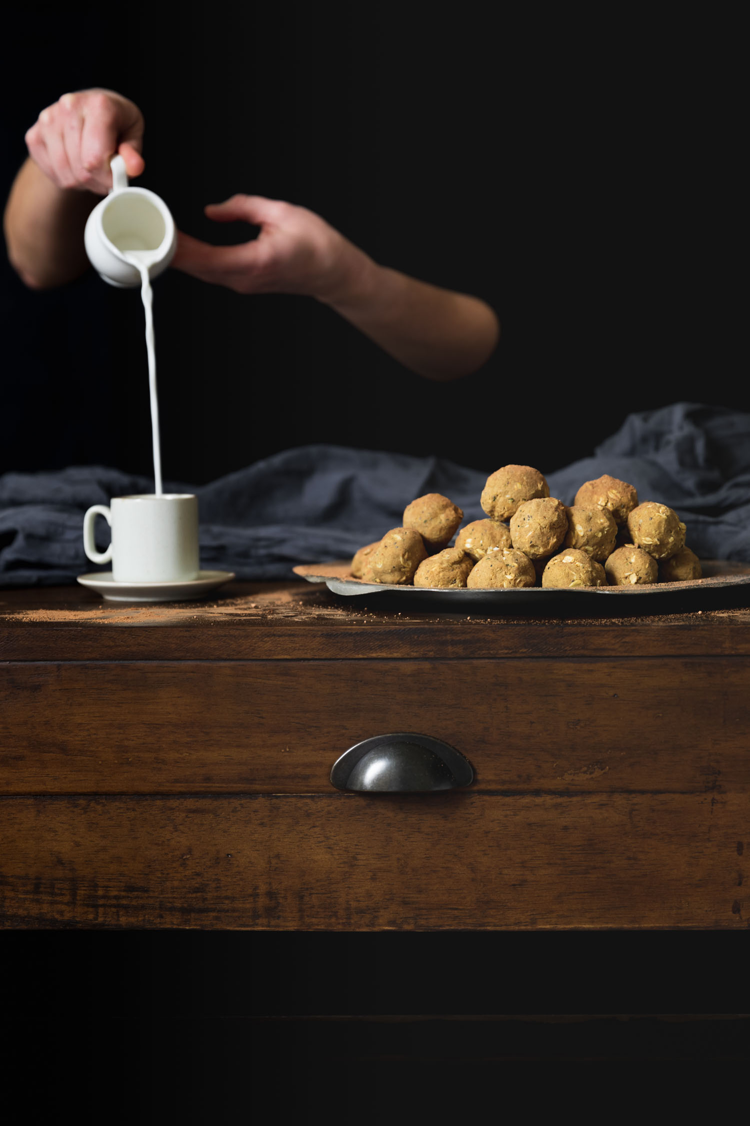 Vertical shot showing no bake peanut butter protein balls in a pile on a table with hands pouring milk into a cup.
