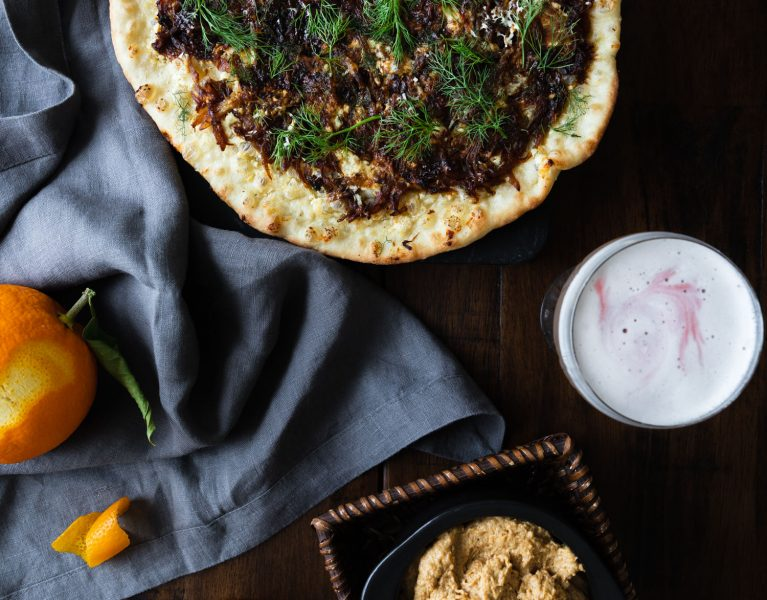 Overhead shot of Caramelized Fennel & Onion Skillet Pizza Recipe surrounded by a cloth napkin, fennel fronds, an orange, drinks, and onion dip.