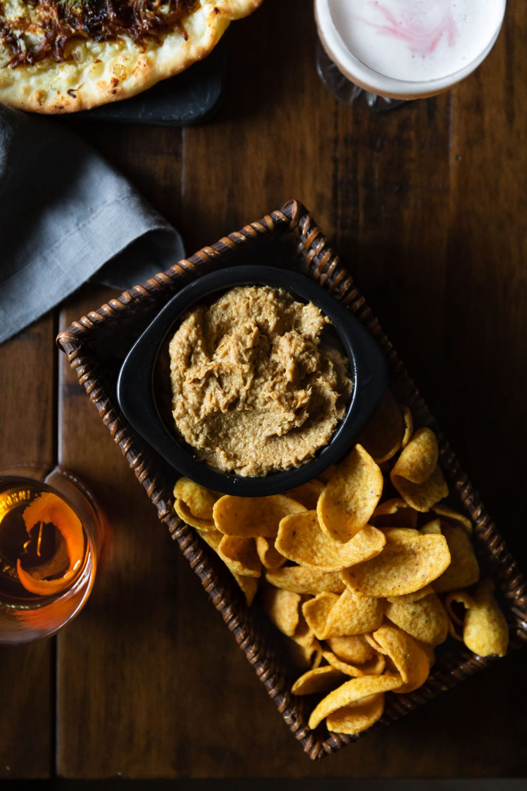Overhead shot of caramelized onion dip in a basket with Fritos.