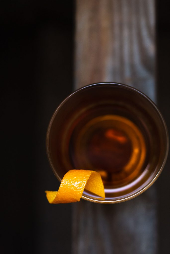 Overhead shot of a Sazerac with an orange peel twist balanced on the edge of the glass.