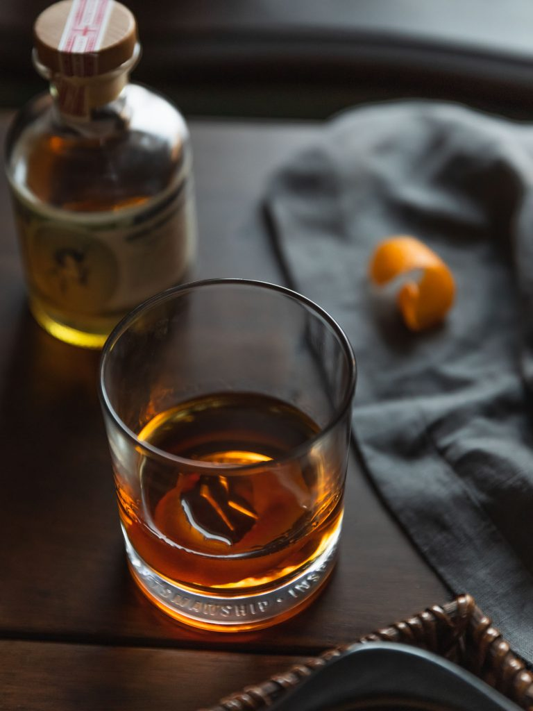 Angled 40 degree shot of a Sazerac in front of a bottle of absinthe and orange peel.