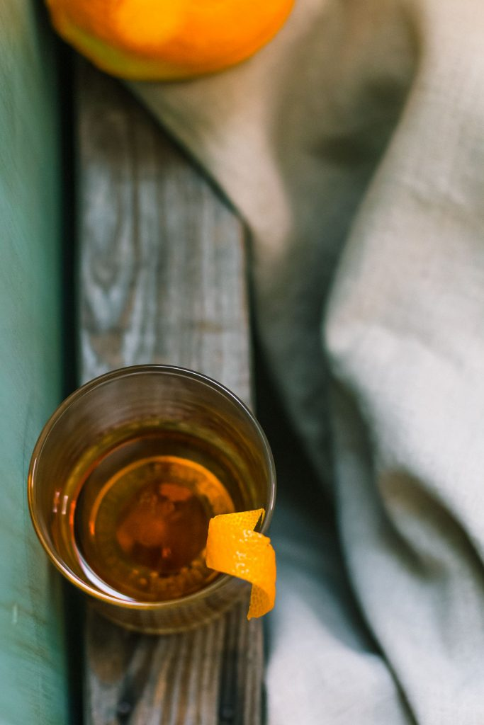 Overhead shot of a Sazerac on a wooden plank surrounded by cloth.