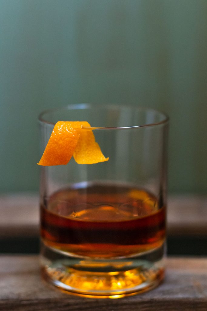 Side head on shot of a Sazerac drink recipe in a rocks glass with an orange peel on the edge.
