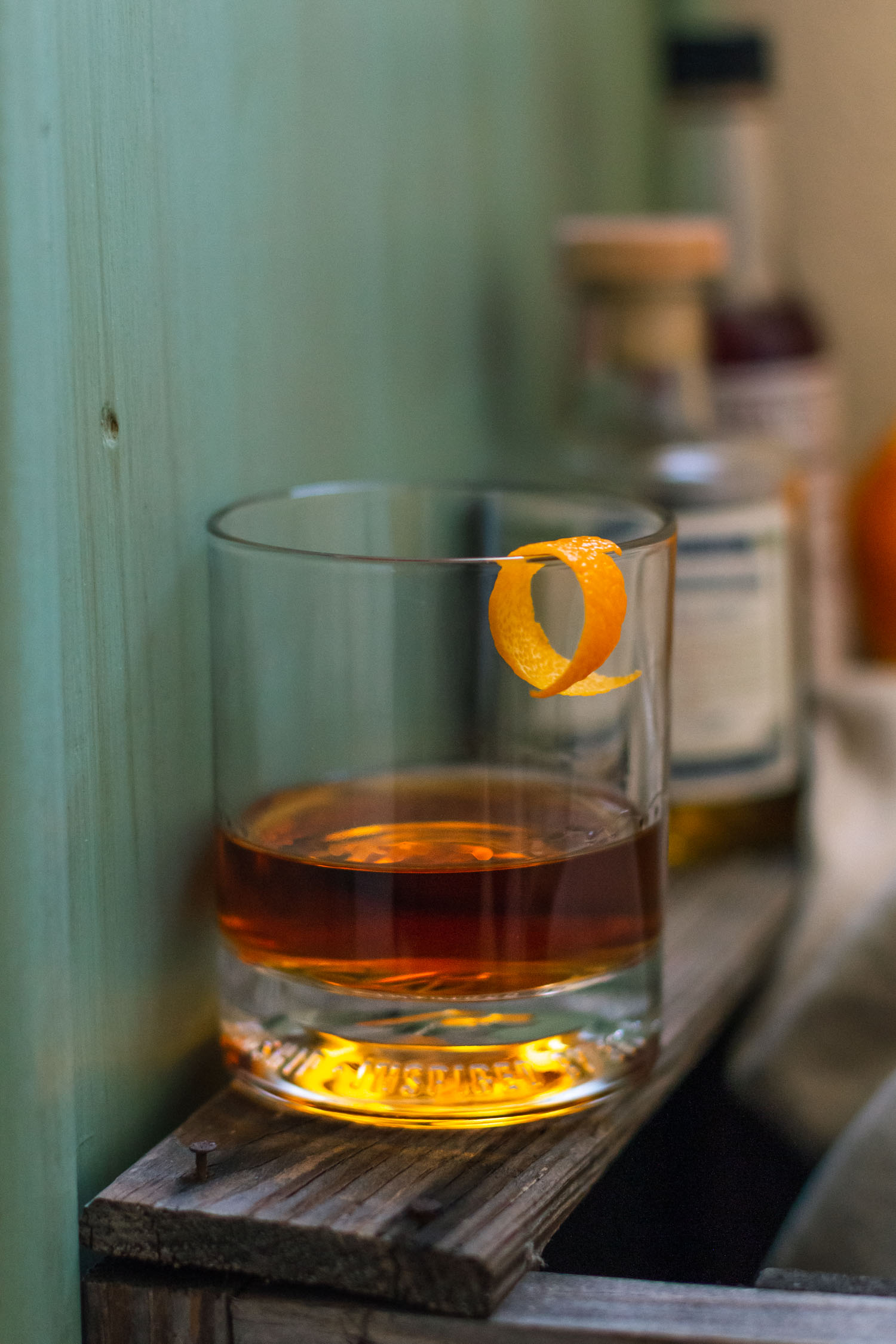 Side vertical shot of a Sazerac drink recipe with absinthe and bitters in the background.