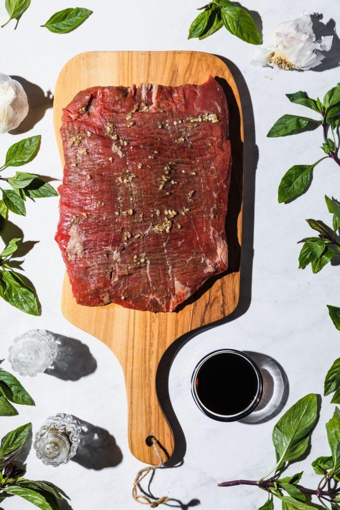 Overhead shot of a slab of raw flank steak on a cutting board.
