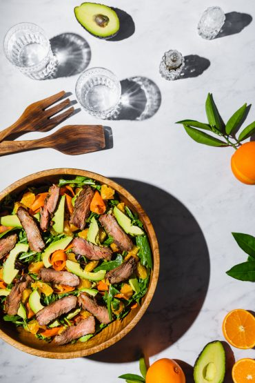 Overhead shot of a flank steak salad in a wooden bowl surrounded by oranges, avocado, and glasses of water.